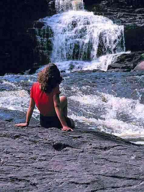 Click for a larger, floating, image of a young woman sitting by a waterfall.